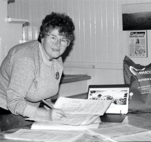 Mme Huguette Lévesque Lamoureux apposant sa signature sur la pétition pour obtenir une bibliothèque à Mascouche. Comité du 250e anniversaire de Mascouche, Collection Huguette Lévesque Lamoureux